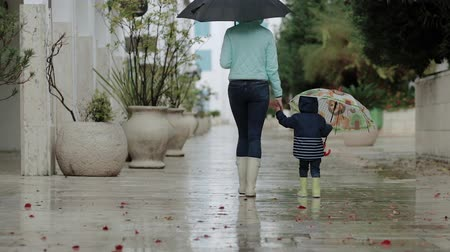 mókás : Mom with her son are walking in the rain in rubber boots and umbrellas.