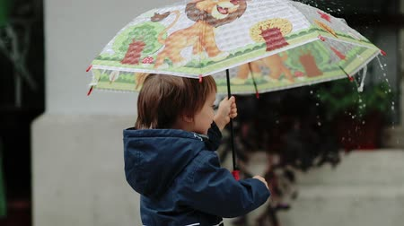 yüz buruşturma : Happy little boy stands under an umbrella during the rain and smiling Stok Video
