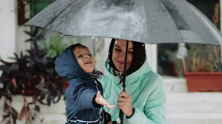 gleba : Young mother with her son hide under an umbrella during the rain Wideo
