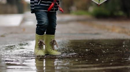 gleba : Little boy walks through puddles in rubber boots during the rain