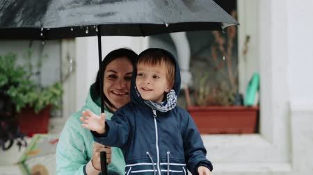 pocsolya : Young mother with her son hide under an umbrella during the rain Stock mozgókép