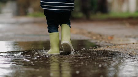 Little boy walks through puddles in rubber boots during the rain