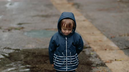 mókás : Little boy walks through puddles in rubber boots during the rain