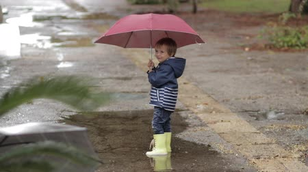 damlar : A boy stands with an umbrella and rubber boots in a puddle in the rain.