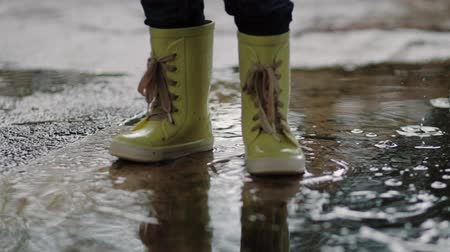 A child in rubber boots stands in a puddle of water in the rain of his feet close-up