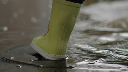 deštivý : A child in rubber boots stands in a puddle of water in the rain of his feet close-up