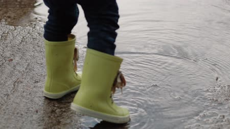 borowina : A child in rubber boots stands in a puddle of water in the rain of his feet close-up