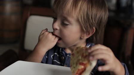 Little boy eats pizza and licks his fingers Dostupné videozáznamy
