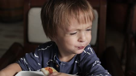 Close up of little cute boy eating pizza. Neutral colors for collor correction. Dostupné videozáznamy