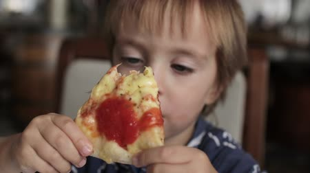 düzeltme : Close up of little cute boy eating pizza. Neutral colors for collor correction. Stok Video