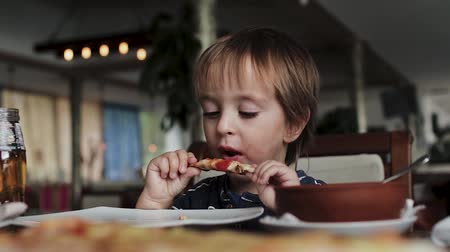 fatia : Close up of little cute boy eating pizza. Neutral colors for collor correction. Vídeos