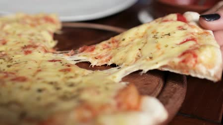 fatia : A womans hand takes a slice of pizza with melted cheese that stretches