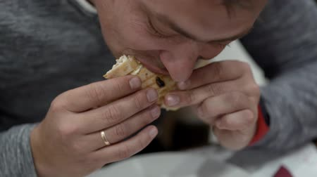étkező : man eats sandwich with chicken with mayonnaise Stock mozgókép