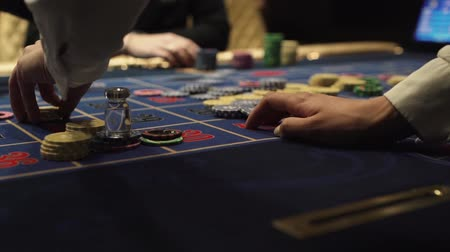Dealer works in the casino moving chips with his hands at the gaming table