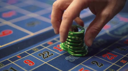 kaszinó : Dealer works in the casino moving chips with his hands at the gaming table