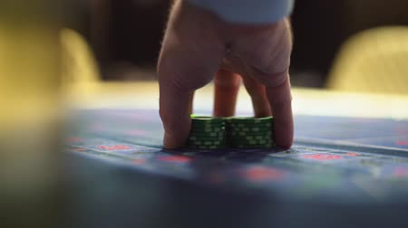 blackjack : Dealer works in the casino moving chips with his hands at the gaming table