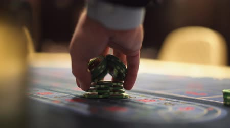 esély : Dealer works in the casino moving chips with his hands at the gaming table