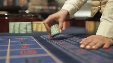 croupier : Dealer works in the casino moving chips with his hands at the gaming table