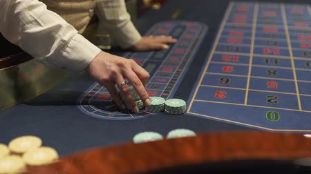 kasyno : Dealer works in the casino moving chips with his hands at the gaming table