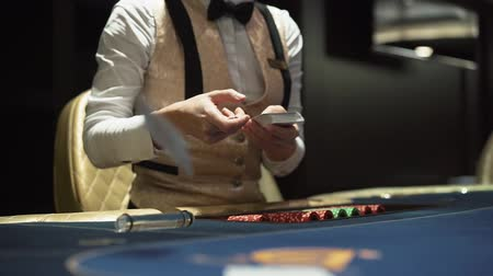 рекламный : Diller hands out cards at the gaming table in the casino Стоковые видеозаписи