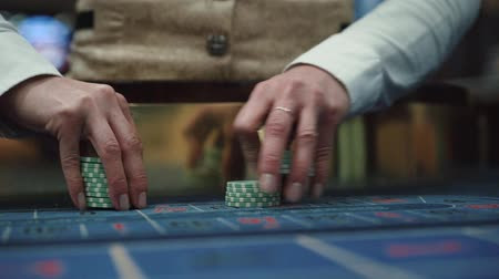 A dealer in a casino holds playing chips with two hands