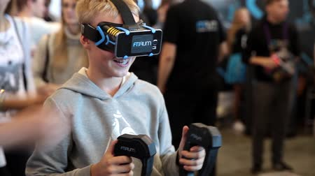 realidade : Young boy playing with virtual reality glasses in Game center. Virtual reality game.