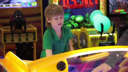 hurl : Little boy playing air hockey game
