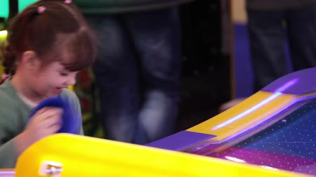hurl : Little girl playing air hockey game