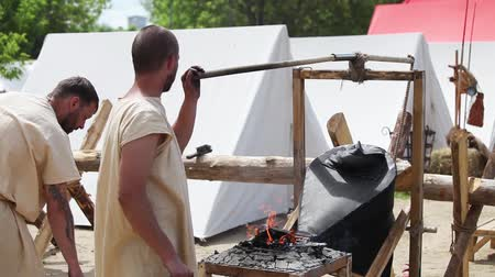 old times : Blacksmiths assistant working with bellows
