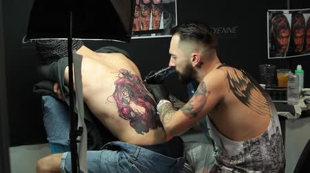 latex gloves : Tattooing on the body. Tattoo artist make tattoo in studio Stock Footage