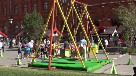 muzeum : Children swinging on a giant swing on Manezh Square in Moscow, Russia