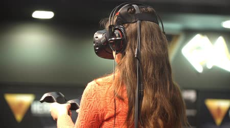 fejhallgató : Girl playing video game with HTC Vive VR glasses. Stock mozgókép