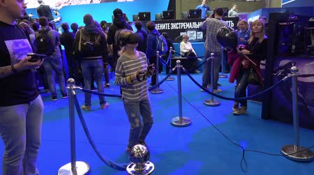 intel : Little girl playing virtual reality game in VR headset with accessories controllers on Intel stand