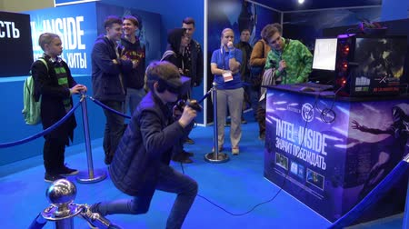 intel : Boy playing virtual reality game in VR headset with accessories controllers on Intel stand