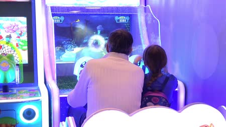 playstation : Daughter and father playing video arcade shooter game Stock Footage