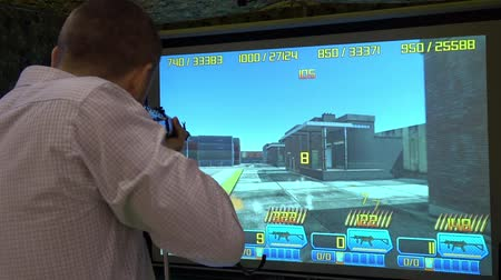 playstation : Man playing video arcade shooting rifle range game