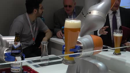 немецкий : Kuka robot arms pouring beer on Messe fair in Hannover, Germany