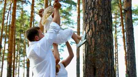 fiatal felnőttek : Young affectionate parents playing with their daughter Stock mozgókép