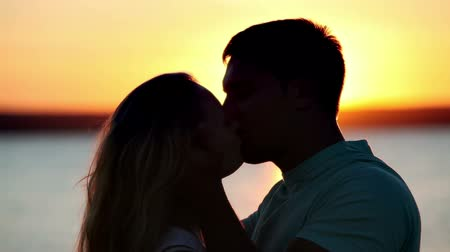 genç çift : Man and woman kissing in the light of sunset Stok Video