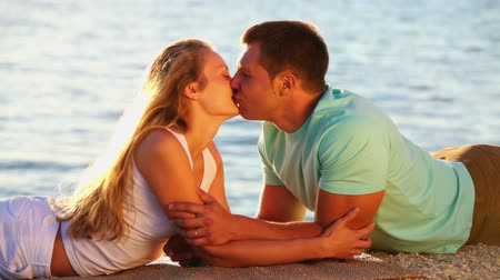 carinho : Beautiful young couple lying by the lake and kissing Vídeos
