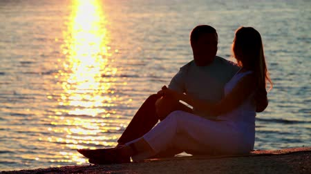 namorado : Young beautiful couple sitting by the sea and kissing in the light of sunset Vídeos