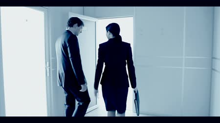 boss : Back view of man and woman going along hallway and coming in a lighted room
