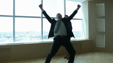 satysfakcja : Businesspeople achieving success and expressing their happiness with a dance