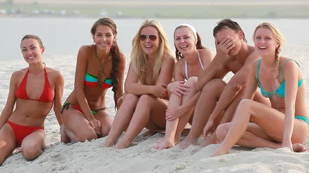 молодые женщины : Group of young people sitting on beach and laughing