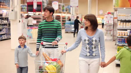 quatro : A family of four rolling a trolley with products along the supermarket, looking around and talking Vídeos
