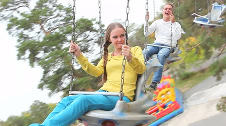teen action : Two teenagers having a good time on a carousel in the park Stock Footage
