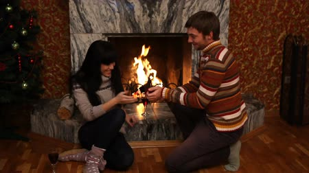 öneri : A young a man proposing to his valentine sitting at a fireplace