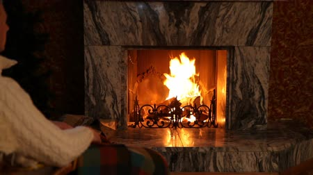 mekan : Man relaxing in rocking chair in front of fireplace in room Stok Video
