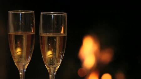 dois objetos : Two flutes with champagne on the background of flame