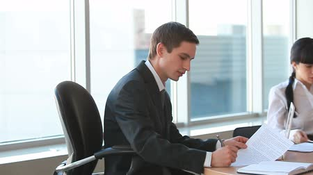 helyek : Businessman interacting with colleague and looking at camera in office